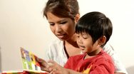 Stock Video Footage of Young Asian Woman Enjoying Reading a Book With Her Son