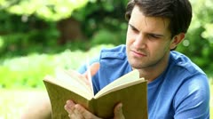 Smiling man reading a fascinating book Stock Footage