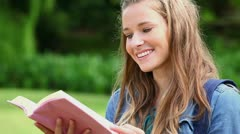 Happy woman reading a fascinating book Stock Footage
