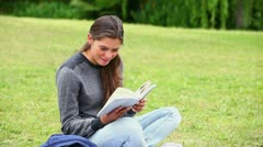 Smiling brunette attentively reading a book Stock Footage