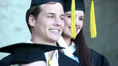 Close-up pan left of graduates holding their diploma - stock footage