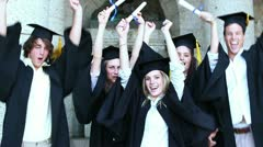 Happy graduates raising arms and jumping Stock Footage
