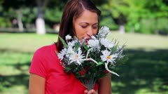 Cheerful woman holding white flowers Stock Footage