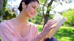 Happy brunette woman reading a novel Stock Footage