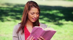 Happy woman reading an interesting novel Stock Footage