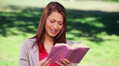 Cheerful woman reading an interesting novel Stock Footage