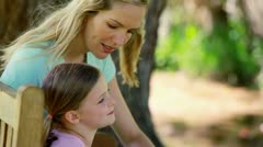 Mother and daughter sitting on a bench Stock Footage