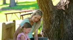 Young woman sitting with her sister on a bench Stock Footage