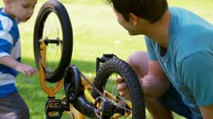 Boy turning a wheel with his father - stock footage