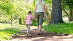 Mother and daughter walking together Stock Footage