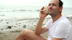 Young happy man with seashell sitting on the beach HD Stock Footage