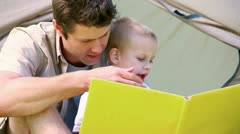 Little boy looking picture book with his father Stock Footage