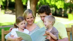 Family looking a picture book on a bench Stock Footage