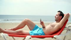 Young man using cellphone while lying on sunbed on beach HD Stock Footage