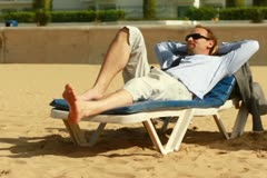 Businessman relaxing on sunbed on the beach, steadicam shot - stock footage