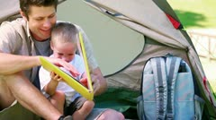 Man with his son looking picture book Stock Footage