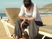 Sad woman sending text message on cellphone by the sea, steadicam shot Stock Footage