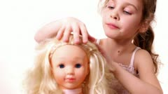Little girl plays with dolls hairdo, isolated Stock Footage