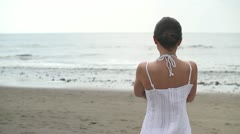 Lonely woman standing at the beach and looking at sea HD Stock Footage