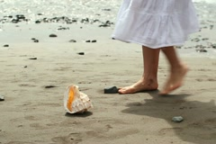 Woman finding beautiful seashell on the beach, slow motion NTSC Stock Footage