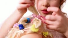 Little girl use elastic band to braid dolls hair Stock Footage