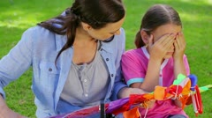 Smiling mother giving a kite to her daughter Stock Footage
