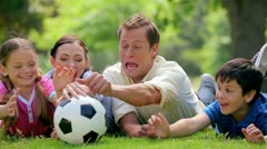 Smiling family trying to catch a soccer ball Stock Footage