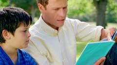 Father and son reading a fascinating book Stock Footage