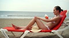 Sexy woman in bikini applying sun block lotion on her body HD Stock Footage