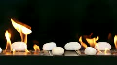 Tongues of flame go through two slots in metal plates with stones on it Stock Footage