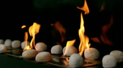 Tongues of flame go through slot in metal plate with stones on it Stock Footage