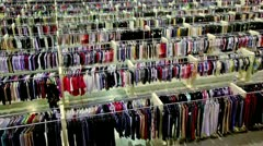 One woman watch goods among lot of clothes in shop - stock footage