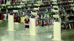 Two women walk in clothes shop with mannequins Stock Footage