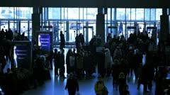 Many people walk around near entrance with glass walls at station Stock Footage