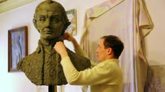 Stock Video Footage of Sculptor Denis Petrov makes mold A.Suvorov bust of clay inside studio
