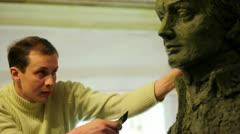 Sculptor Denis Petrov corrects unfinished A.Suvorov bust with knife Stock Footage