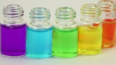 Six transparent open bottles moves sideward with color oil on them Stock Footage