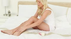 Blonde young woman applying moisturiser on her legs Stock Footage
