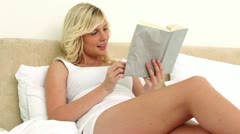 Young blonde woman reading a novel Stock Footage