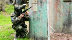 Boy paintball player sits in ambush behind metal fence and looks around Stock Footage
