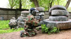 Two boys paintball players sit in ambush behind pile of tyres Stock Footage