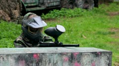 Boy paintball player sits in ambush behind metal fence Stock Footage