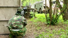 Boy paintball player sits in ambush in at background of old carrier Stock Footage