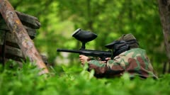 Boy paintball player sits in ambush with gun at background of leaves Stock Footage