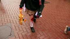 Girl walks by pavement with bloody legs and carries soft toy Stock Footage