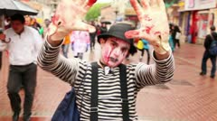 Bloody zombie mime walk by street among people during Zombie Parade Stock Footage