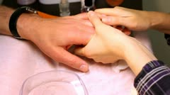 In course of manicure cosmetician rubs butter for nails in of man fingers Stock Footage