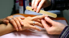 Stock Video Footage of Manicure technician does manicure for client by means of file for nails