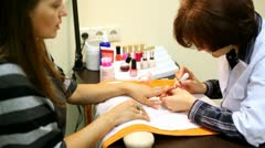 Cosmetician accurately covers nails of client with transparent nail polish - stock footage