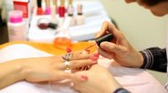 Cosmetician accurately covers nails of client with pink nail polish Stock Footage